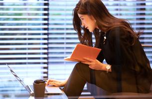 手帳を手にパソコンを見る女性の写真素材 [FYI03152567]