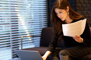 書類を手にパソコンを見る女性の写真素材 [FYI03152568]