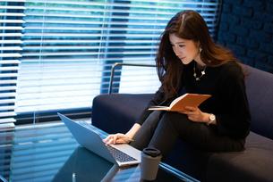 手帳を手にパソコンを見る女性の写真素材 [FYI03152570]