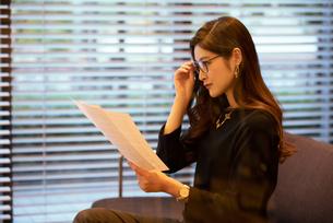 書類を読む女性の写真素材 [FYI03152571]
