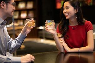 お酒を飲みながら会話する男女の写真素材 [FYI03152572]