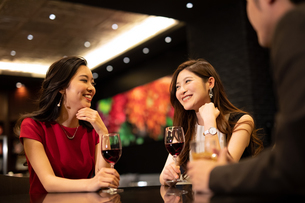 お酒を飲みながら会話する男女の写真素材 [FYI03152574]
