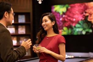 グラスを持って会話する男女の写真素材 [FYI03152575]