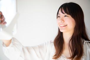 鏡を見ながら笑っている女性の写真素材 [FYI03153401]