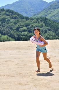 砂浜を走る女の子(海水浴、水着)の写真素材 [FYI03153590]