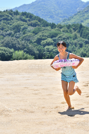 砂浜を走る女の子(海水浴、水着)の写真素材 [FYI03153591]