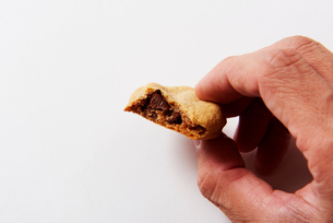 チョコチップクッキーをつまむ男性の写真素材 [FYI03153816]