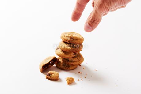 チョコチップクッキーをつまもうとしている男性の写真素材 [FYI03153819]