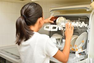 食洗器で食器を洗浄する女の子(後姿)の写真素材 [FYI03154417]