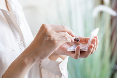ファンデーションを持つ女性の手の写真素材 [FYI03155706]