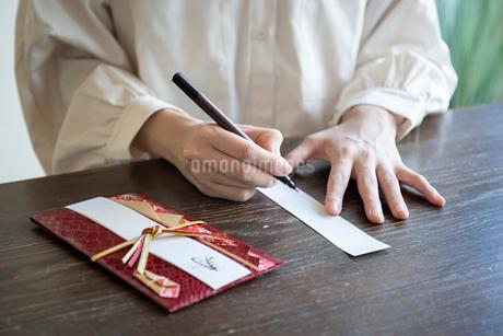 ご祝儀袋に記名する女性の手元の写真素材 [FYI03155714]
