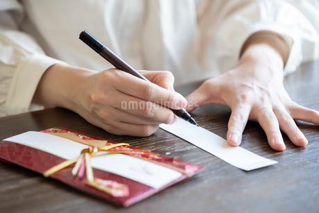 ご祝儀袋に記名する女性の手元の写真素材 [FYI03155715]