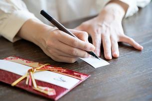 ご祝儀袋に記名する女性の手元の写真素材 [FYI03155716]