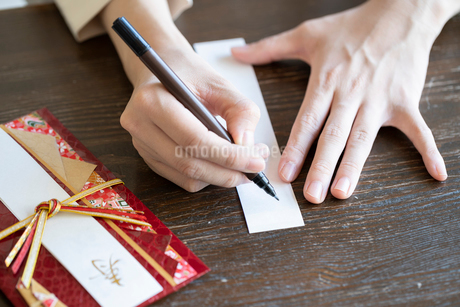 ご祝儀袋に記名する女性の手元の写真素材 [FYI03155717]