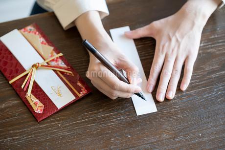 ご祝儀袋に記名する女性の手元の写真素材 [FYI03155718]