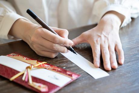 ご祝儀袋に記名する女性の手元の写真素材 [FYI03155719]