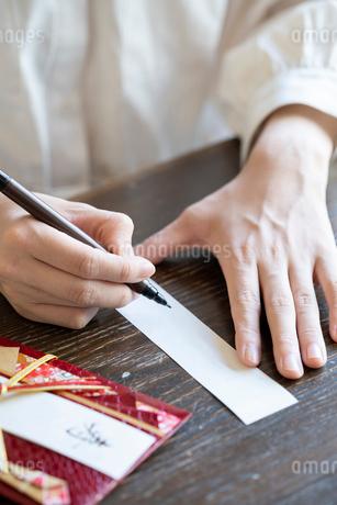 ご祝儀袋に記名する女性の手元の写真素材 [FYI03155720]