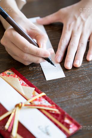 ご祝儀袋に記名する女性の手元の写真素材 [FYI03155721]