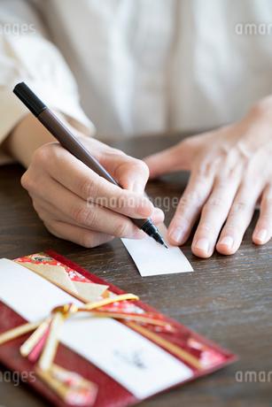 ご祝儀袋に記名する女性の手元の写真素材 [FYI03155722]