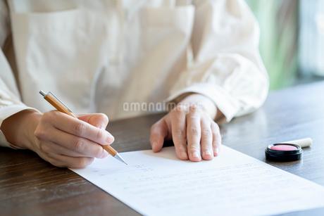 書類に記名する女性の手元の写真素材 [FYI03155725]