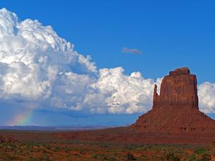 米ユタ州モニュメントバレーのビュートの背景に広がる雷雲と虹の風景の写真素材 [FYI03156241]