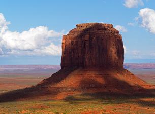 米ユタ州モニュメントバレーのビュート岩山のひとつに雲の陰が流れ覆っている景色の写真素材 [FYI03156248]