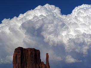 夏の躍動感溢れる雲が大きな雷雲になって見える米ユタ州モニュメントバレーのビュート、岩の山が見える景色の写真素材 [FYI03156249]