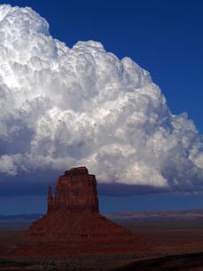 米ユタ州モニュメントバレーのビュートと呼ばれる岩山の背景で成長する巨大な雲の風景の写真素材 [FYI03156253]