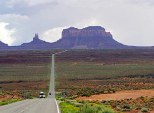 米ユタ州モニュメントバレーを走るハイウエーと背景に見えるビューとの景色の写真素材 [FYI03156263]