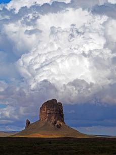 米アリゾナ州モニュメントバレー付近のビュートの背景に大きく成長する雲の景色の写真素材 [FYI03156276]