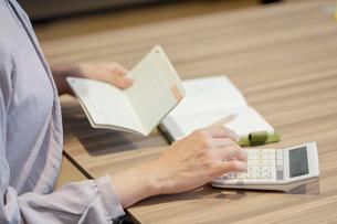 通帳をを見ながら電卓を打つ女性の手元の写真素材 [FYI03156525]