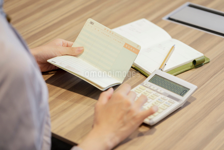 通帳をを見ながら電卓を打つ女性の手元の写真素材 [FYI03156526]