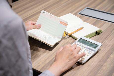 通帳をを見ながら電卓を打つ女性の手元の写真素材 [FYI03156527]