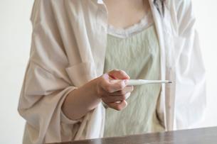 体温計で熱を測る女性の手元の写真素材 [FYI03156571]