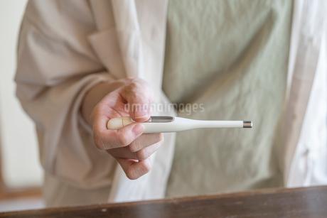 体温計で熱を測る女性の手元の写真素材 [FYI03156572]