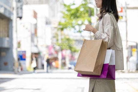 ショッピングで買い物袋をたくさん持つ女性の手元の写真素材 [FYI03156574]