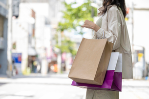 ショッピングで買い物袋をたくさん持つ女性の手元の写真素材 [FYI03156575]