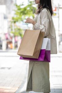ショッピングで買い物袋をたくさん持つ女性の手元の写真素材 [FYI03156576]