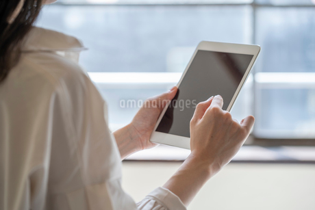 タブレットを操作する女性の手元の写真素材 [FYI03156580]