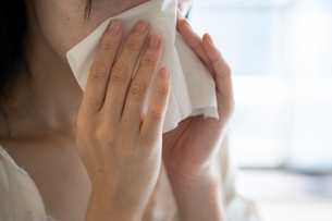 ティッシュで鼻をかむ女性の手元の写真素材 [FYI03156583]