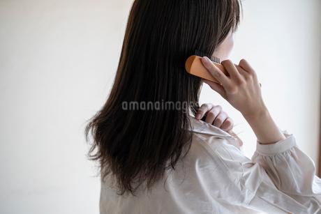 髪の毛をブラシで解く女性の後ろ姿の写真素材 [FYI03156585]