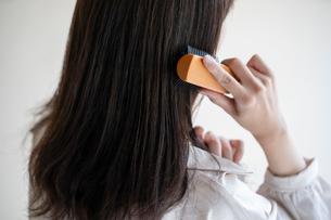 髪の毛をブラシで解く女性の後ろ姿の写真素材 [FYI03156586]