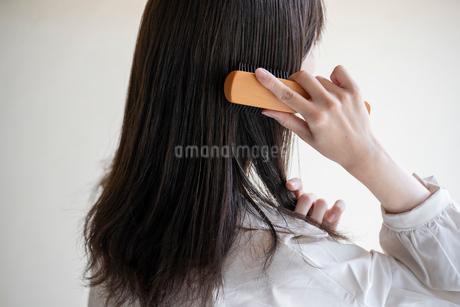 髪の毛をブラシで解く女性の後ろ姿の写真素材 [FYI03156587]