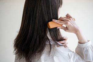 髪の毛をブラシで解く女性の後ろ姿の写真素材 [FYI03156589]