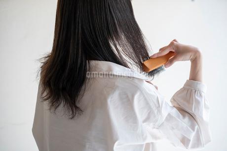 髪の毛をブラシで解く女性の後ろ姿の写真素材 [FYI03156593]