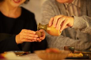 日本酒で晩酌をするシニア夫婦の手元の写真素材 [FYI03159992]
