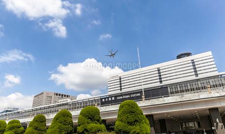 新大阪駅の駅舎と上空を飛ぶ飛行機の写真素材 [FYI03160048]