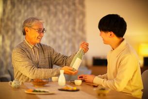 息子から日本酒のプレゼントをされる父親の写真素材 [FYI03160073]