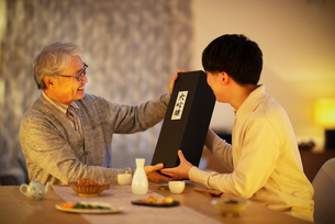 息子から日本酒のプレゼントをされる父親の写真素材 [FYI03160077]