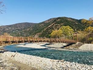 晴れた日の山と川に架かる木造の橋の写真素材 [FYI03160343]